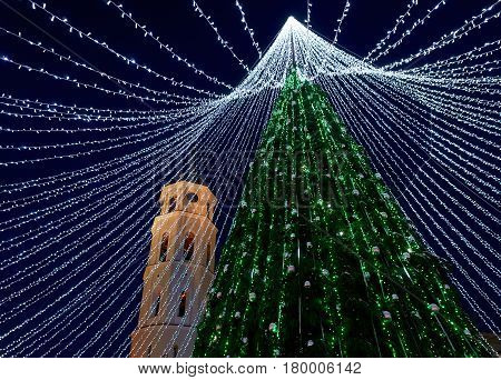Christmas tree with decoration and Bell tower at Cathedral Square in Vilnius Lithuania. It has fairy lights as if bridal veiling. Illuminated late in the evening