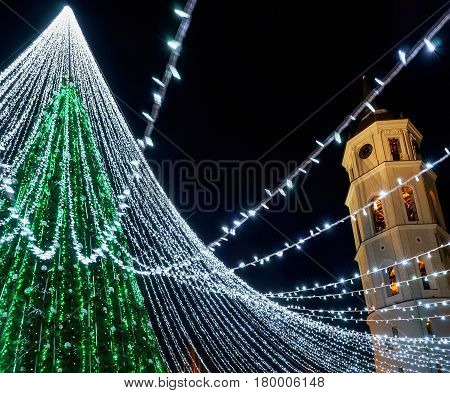 Christmas tree with decoration and Bell tower at Cathedral Square in Vilnius Lithuania. It has fairy lights as if bridal veiling. Illuminated at night