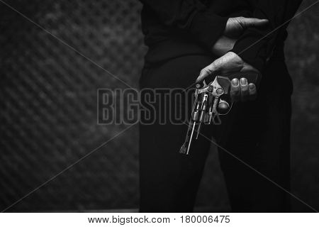 Plotting a crime. Lawless scary hateful villain holding a gun in his hand hiding it behind his back while waiting for his victim