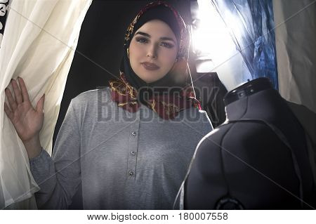 Female fashion designer tailoring conservative clothing in a textile workshop. The hijab she is wearing is associated with muslims middle east or eastern european cultures. The image depicts creativity and professional seamstress craft.