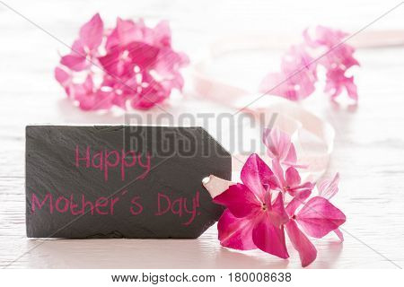 Plate Of Slate With English Text Happy Mothers Day. Spring Flower Blossom Of Hydrangea. Shiny White Wooden Background
