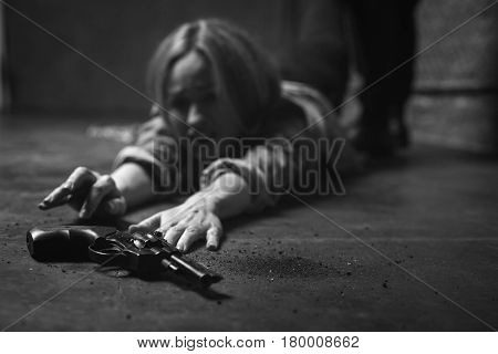 My only chance. Weak stubborn trapped girl stretching her hand to a gun lying in front of her while trying protecting herself