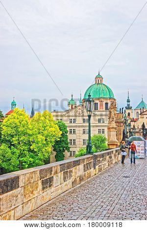 People On Charles Bridge Over Vltava River In Prague Church