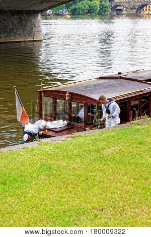 Skipper Repairing Excursion Boat At Embankment Of Vltava River Prague