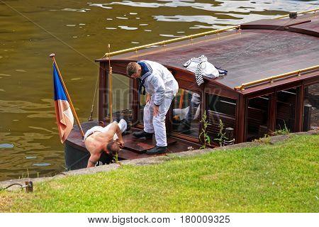 Skipper Repairing Excursion Ferry At Embankment Of Vltava River Prague