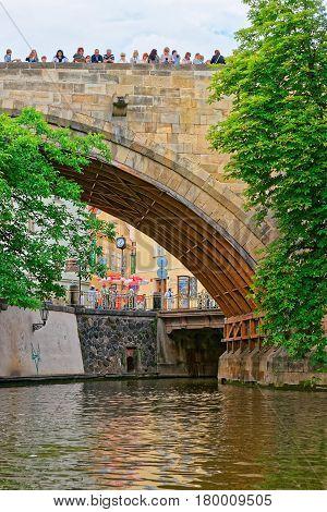 Tourists On Charles Bridge Over Vltava River In Prague