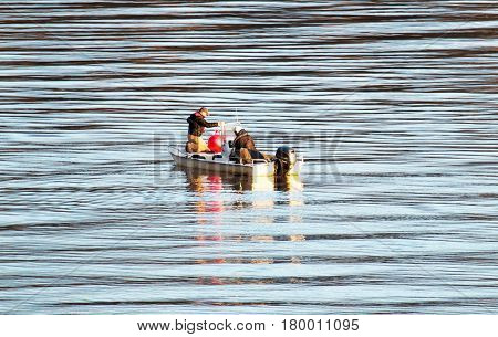 Two men in a boat check their crab traps on a river in outside of Georgetown