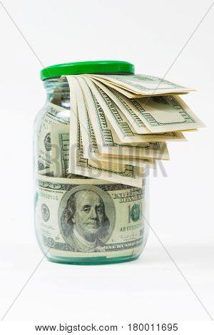 Many 100 US dollars bank notes in a glass jar isolated on white background.