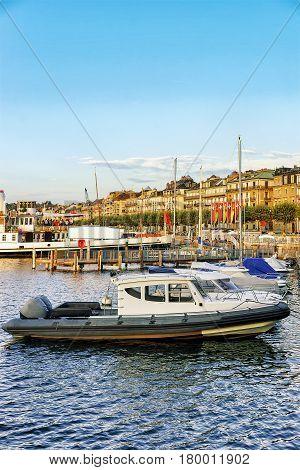 Boat On Geneva Lake Near Embankment Of Promenade Du Lac