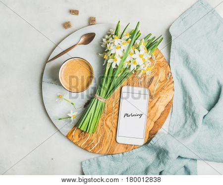 Cup of morning coffee, bucket of spring flowers and mobile phone with text Morning on serving board over light grey marble background, top view. Morning greeting card concept