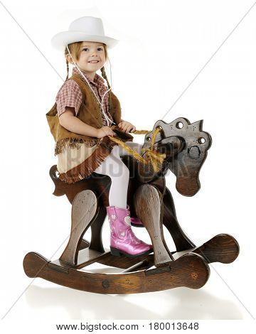 An adorable preschool cowgirl sitting pretty on her wooden rocking horse.  On a white background.