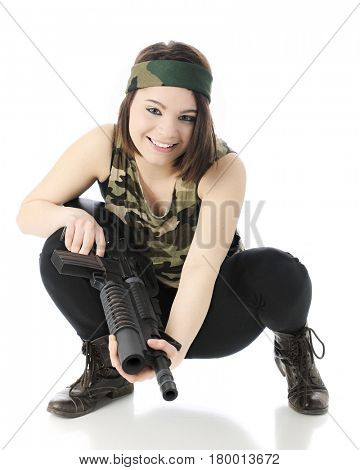 A beautiful teen girl, happily squatting in her camouflage shirt and headband while holding a machine gun.  On a white background.