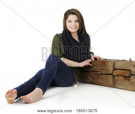 A beautiful, barefoot teen girl happily sitting on the ground, leaning on a rustic old beam.  On a white background.