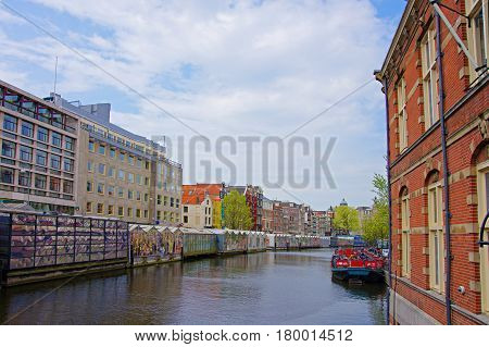 Water boat in canal of Amstel River and buildings at embankment Amsterdam Netherlands.