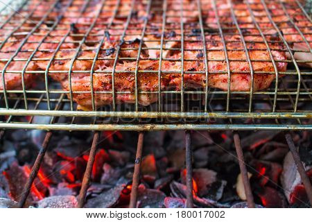 Grilled pork ribs on fireplace closeup photo. Red meat barbecue cooking. Outdoor grill meat. Juicy meat food. Summer picnic background. Tasty pork BBQ. Brown pork chops baked on bonfire image