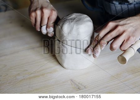 Woman hands close-up forming crude clay in a potter's workshop studio. Craft-work