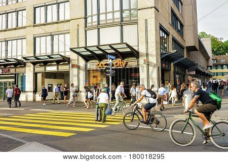 People Riding Bicycles At Bellevue Bus Stop In Zurich