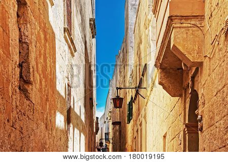 Narrow Silent Street With Lanterns And Balcony In Mdina