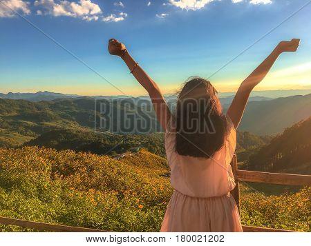 Asia teenage girl relax at Mexican sunflower field on Mae u Kho mountain Mae Hong Son Thailand.