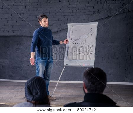 Young speaker man talking to audience during conference. He is giving a lecture and showing graph on flipchart. Business presentation concept. He is wondering