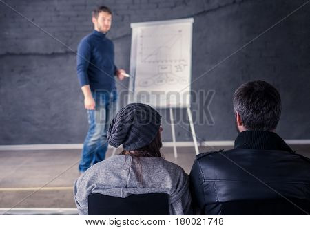 Close up view of student audience with speaker man on background. He is giving a lecture and showing graph on flipchart. Business presentation concept