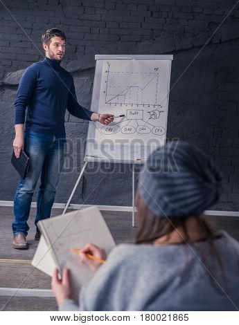 Young speaker man talking to audience during conference. He is giving a lecture. and showing graph on flipchart. teacher. Business presentation concept