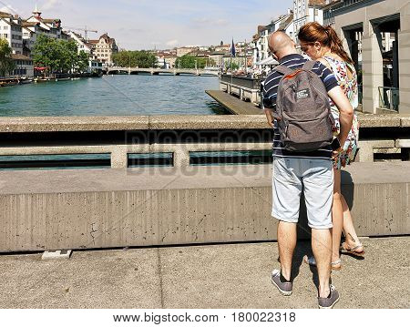 People With City Map At Limmat River Embankment Zurich