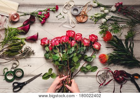 Carnations, red roses, white roses, purple callas on a white wooden table in a flower shop