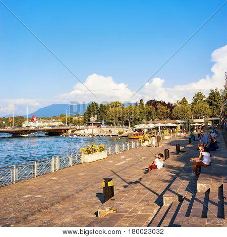People Sitting On Embankment At Geneva Lake In Summer Switzerland