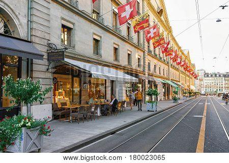 Rue De La Corraterie Street With Swiss Flags Geneva
