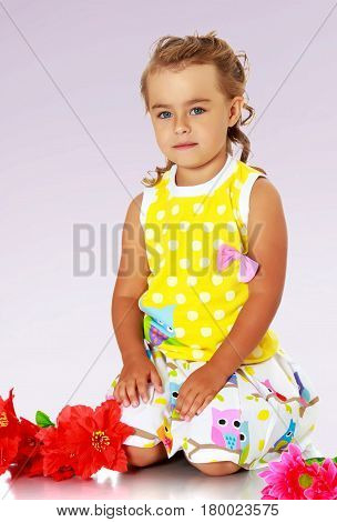 Beautiful little girl in a yellow summer dress kneeling on the floor. Beside her lay a red artificial flowers.Not a purple gradient background.
