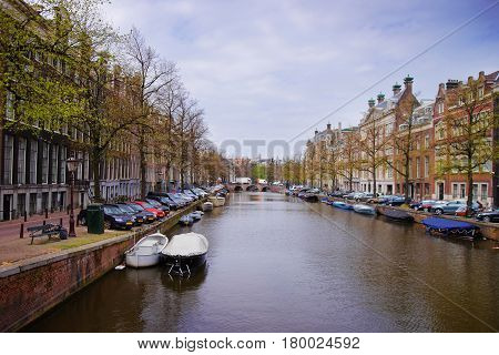 Boats On Canal Of Amstel River And Buildings Amsterdam
