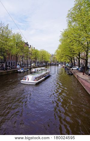 Boats On Canal Of Amstel River And Buildings In Amsterdam