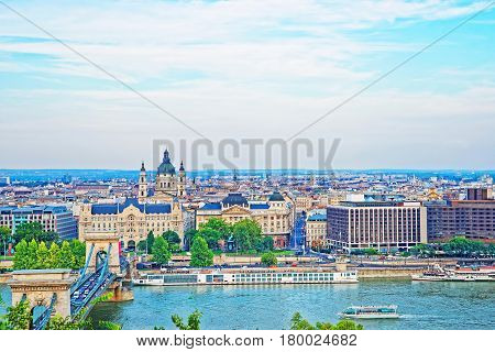 Chain Bridge over Danube Canal and St Stephen Basilica at Pest city center in Budapest Hungary