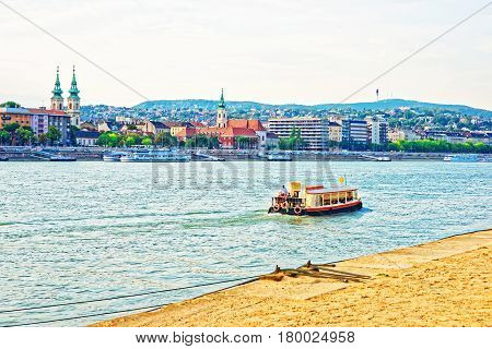 Ferry And Buda City With University Church Towers At Danube