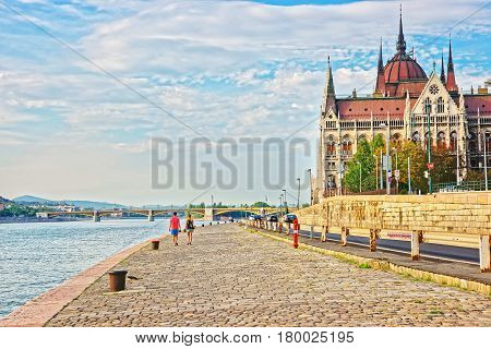 Hungarian Parliament Building And People At Danube River Embankment Budapest