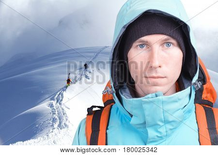 Alpinist man with a backpack on a background of mountain scenery. Looking at the camera.