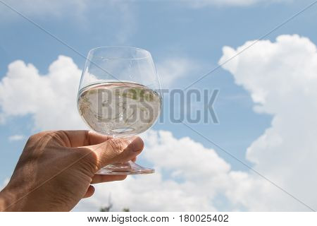 hand holding glass of water on sky background