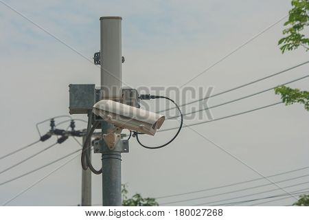 Closed-circuit camera on electric pole and walkway in public park.