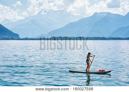 Girl Standing On Standup Paddle Surfing On Geneva Lake Montreux