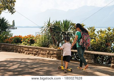 Little Boy With Scooter And Mother At Geneva Lake Montreux