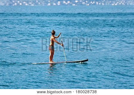 Girl standing on standup paddle surfing in Geneva Lake in Montreux Switzerland