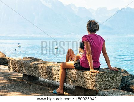 Mother And Daughter Sitting On Bench At Geneva Lake Montreux