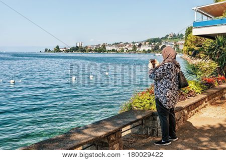 Woman Taking Photos Of Geneva Lake In Montreux