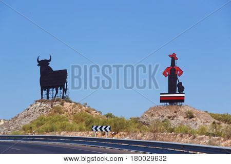 Bull metal figure and man with hat and guitar figure along the road in Seville Andalusia Spain.