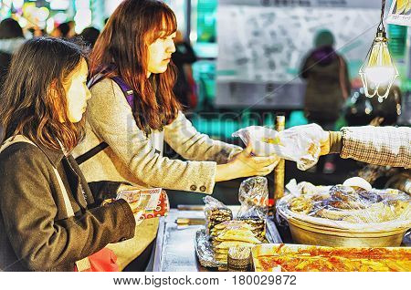 Seoul South Korea - March 14 2016: Korean girls buying street food in Myeongdong open street market in Seoul South Korea. Selective focus. Selective focus