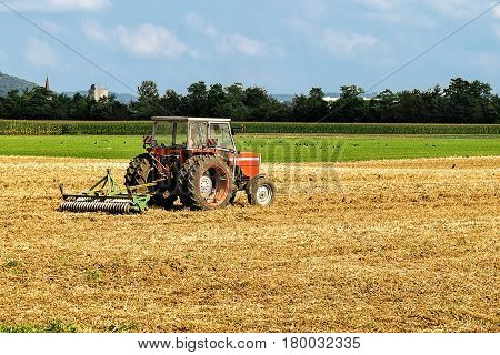 Tractor with plough doing agricultural seasonal work in the field.