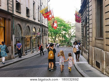 Family At Street With Flags On Hotel Ville At Geneva