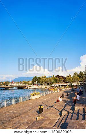 People Sitting On Embankment Of Geneva Lake In Summer