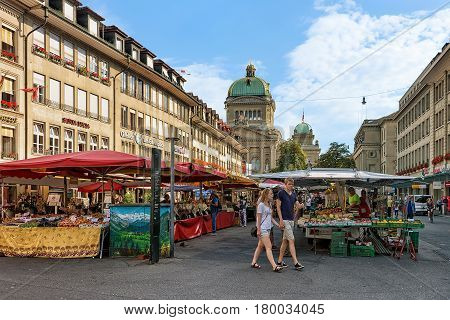 Market With People And Swiss Parliament Building In Bern